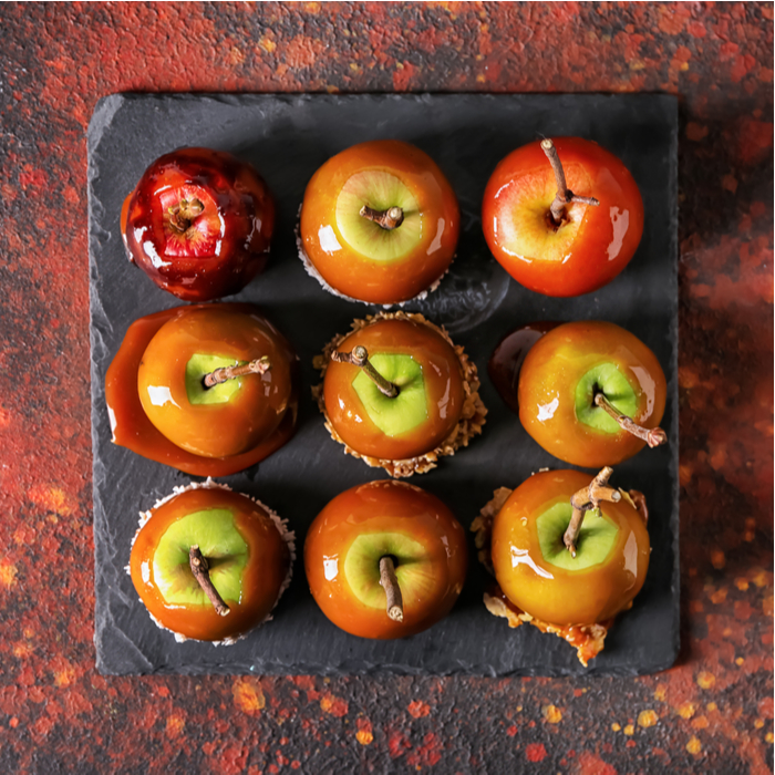 Nine unique caramel apples on a slate serving plate on an abstractly marbled background of fall colors.