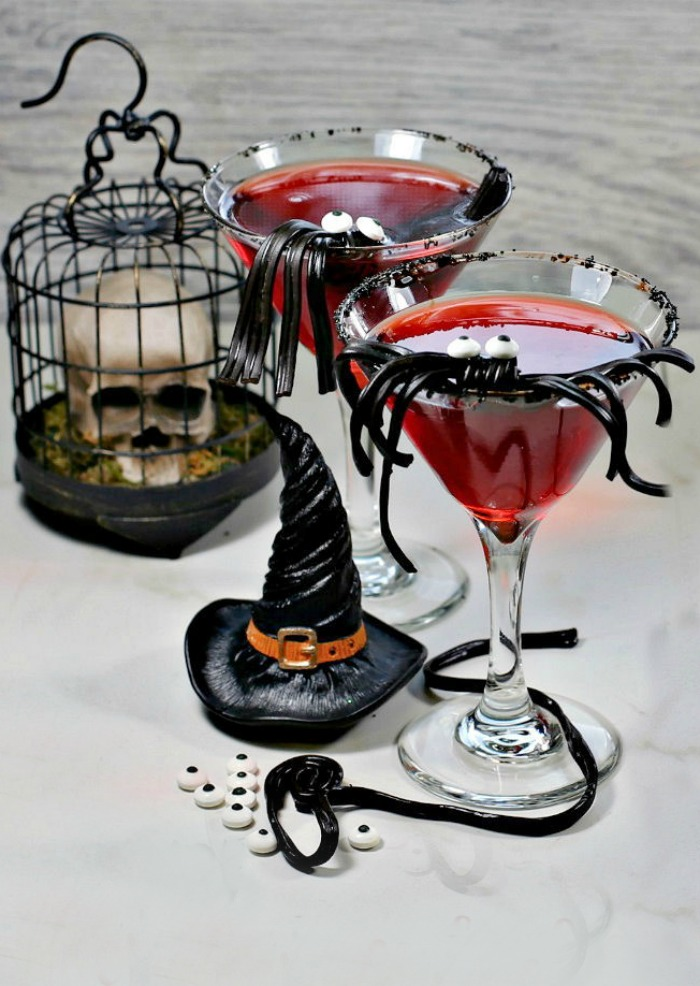Red drink with a spider garnish, skull and witches hat.