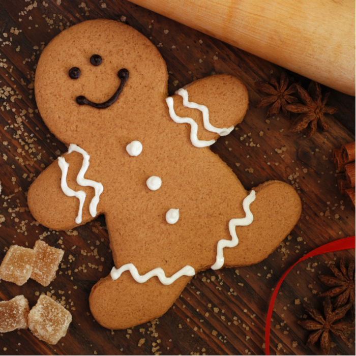 A closeup shot of a gingerbread cookie on a wooden table next to a rolling pin, ginger candies, star anise and a red ribbon.