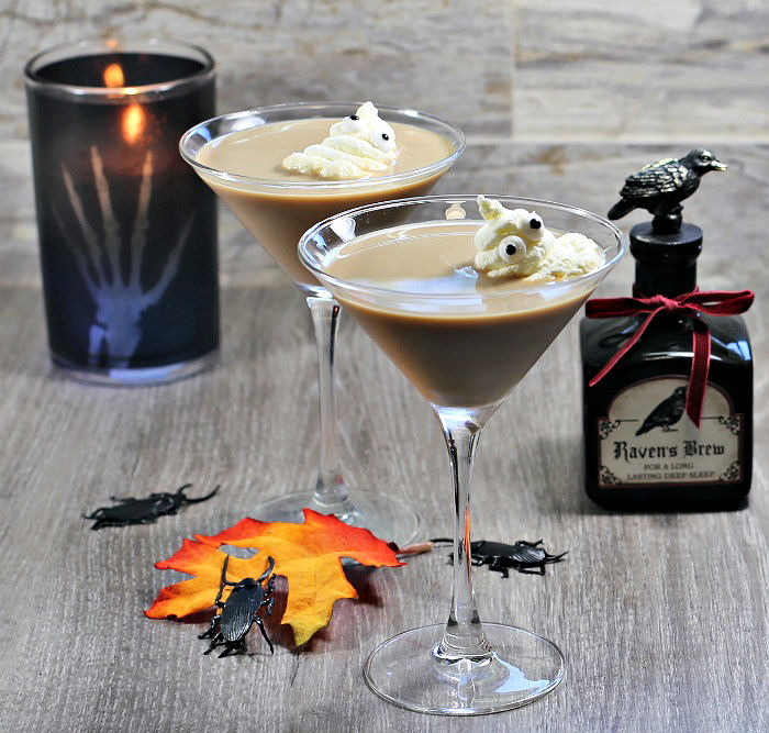 Whipped cream ghosts in a creamy drink, with black candle leaves and bottle of potion.