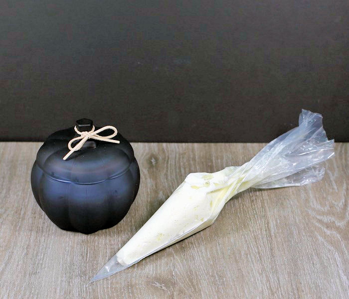 Whipped cream in a piping bag with a black pumpkin candle.