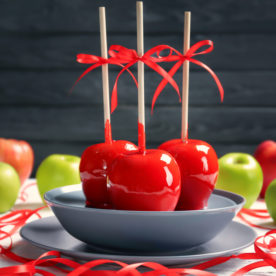 Three candy apples for Christmas with bows on them, on a plate.