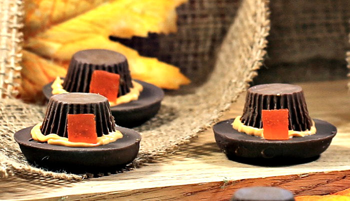 Three pilgrim hat dessert cookies on a wooden board with burlap and leaves.