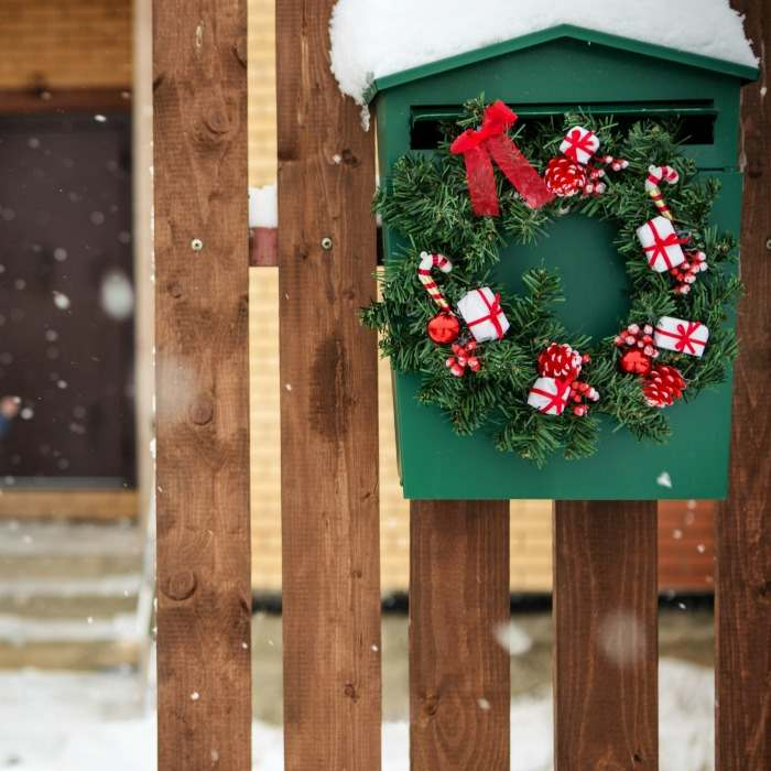 Green antique letterbox with small Christmas wreath.
