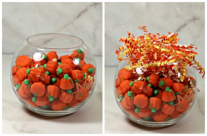 Fish bowl filled with candy pumpkins and crinkle-cut orange and yellow shredded paper.