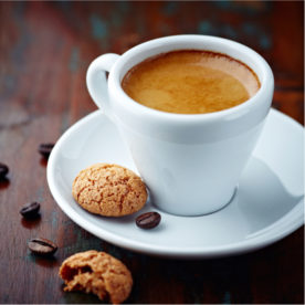 A shot of espresso with a small biscotti beside it on a saucer.