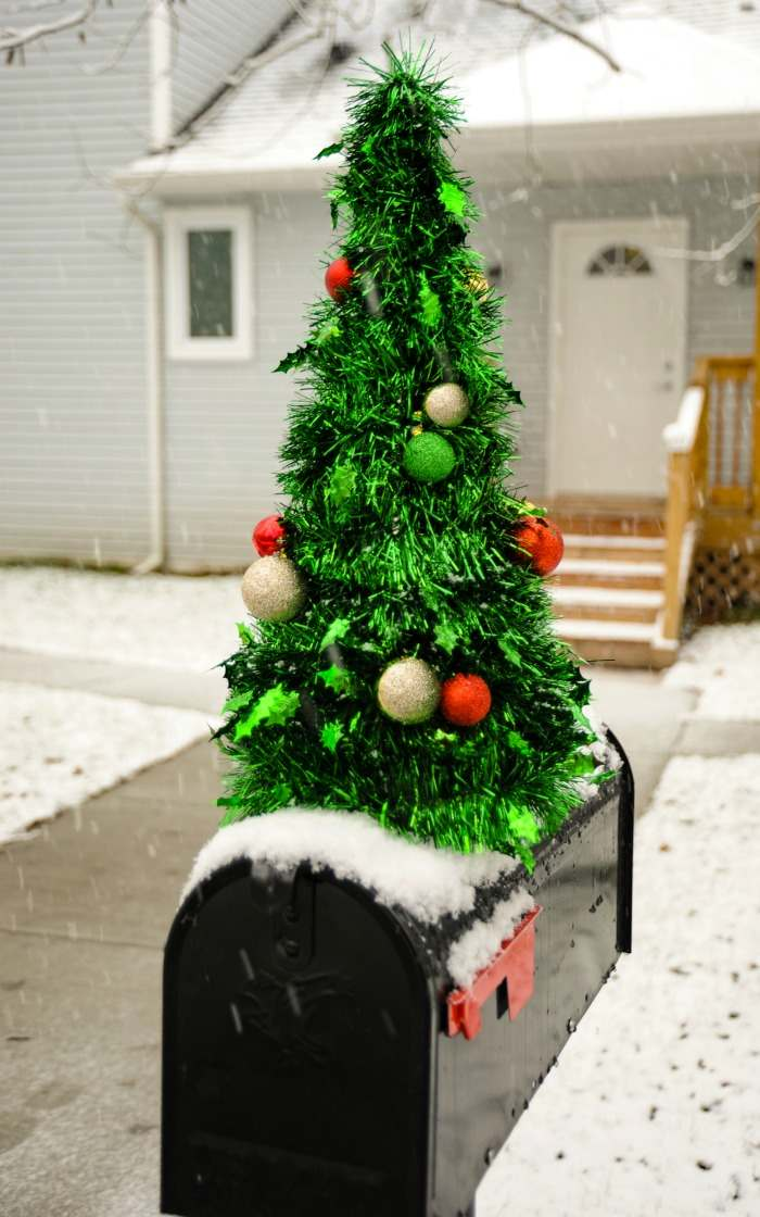 Decorating a mailbox for Christmas with a Metallic Christmas tree on a black mailbox.