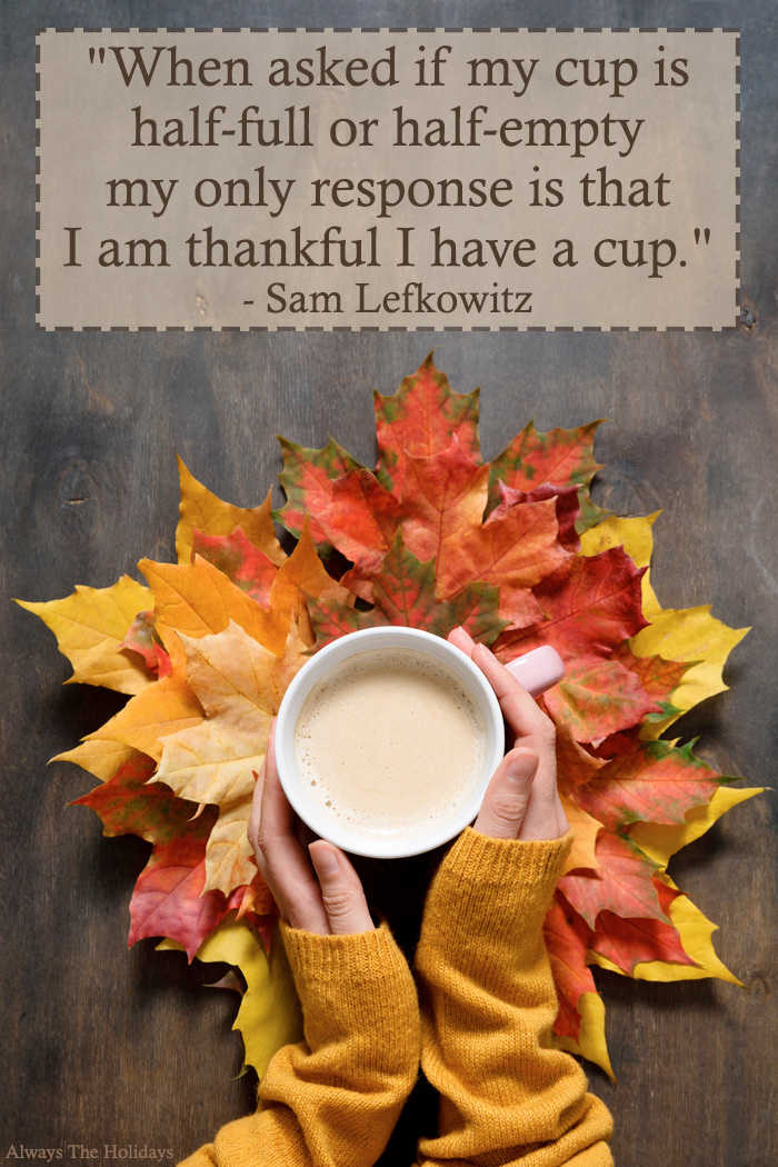 "A woman's hands holding a latte over leaves with a Thanksgiving quote text overlay reading ""When asked if my cup is half-full or half-empty my only response is that I am thankful I have a cup.""."