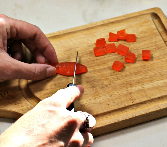 Female hands cutting Swedish fish into squares on a cutting board.