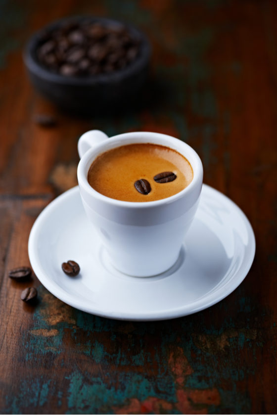 An espresso shot with espresso beans on top for National Espresso Day.