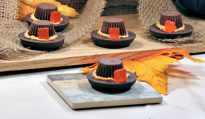 Pilgrim hat cookie treats with leaves and a wooden board.