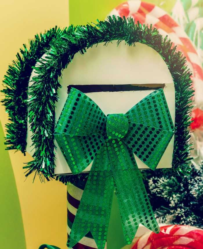 White mailbox with green garland and metallic bow.