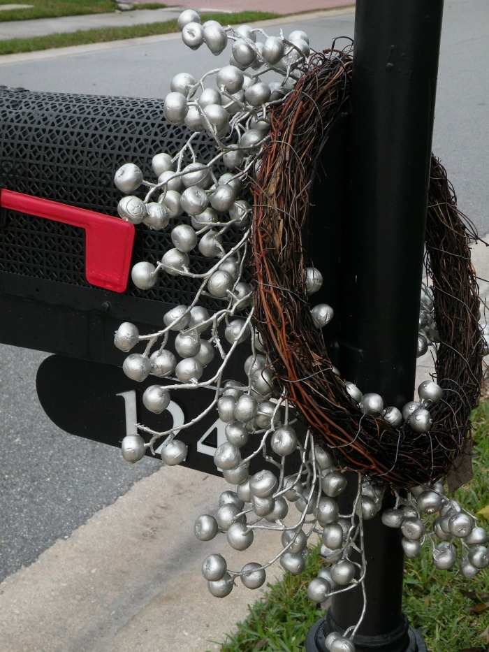 Grape wreath on mail box post with silver berry garland wrapped around.