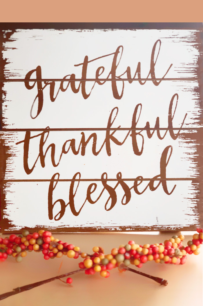 "A wooden decor board with the Thanksgiving quote ""Grateful, thankful, blessed"" painted on it."
