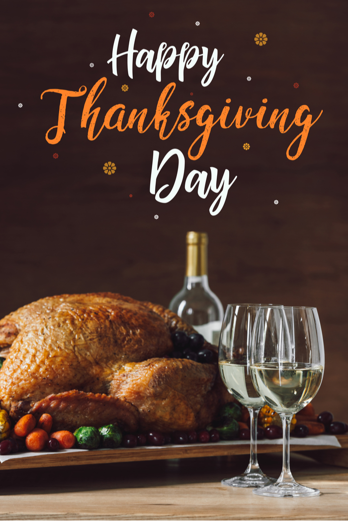 A happy Thanksgiving day quotes on a photo of a Thanksgiving turkey next to a bottle and two glasses of white wine.
