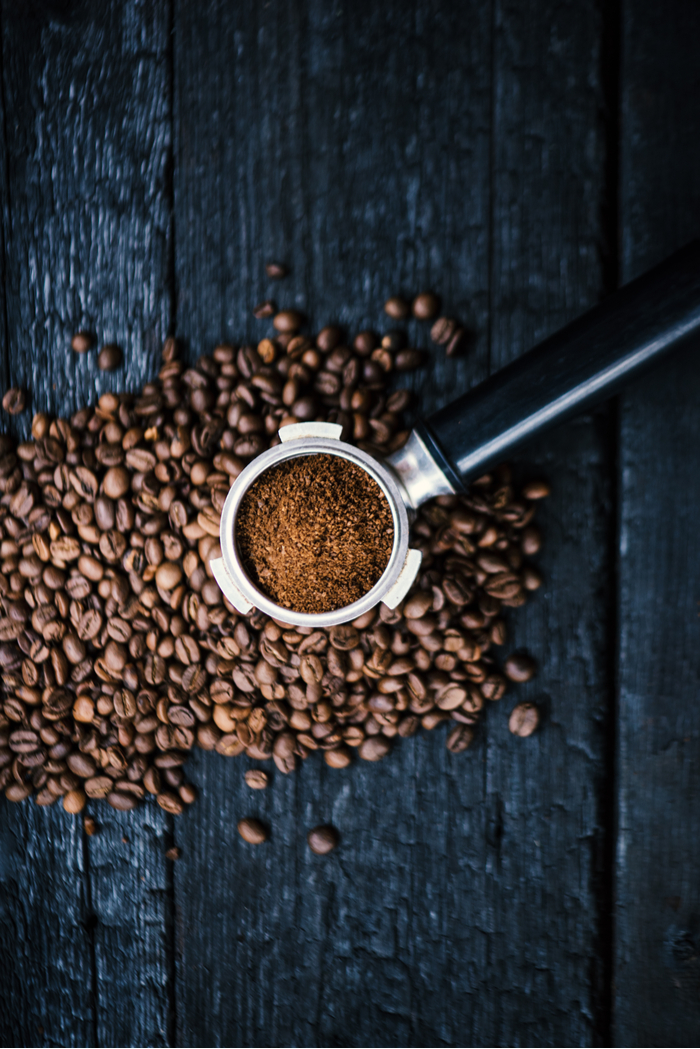 A portafilter filled with espresso grounds over coffee beans on a dark wooden background.