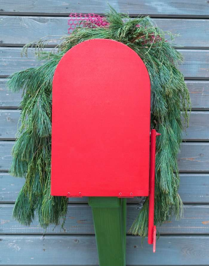 Red mail box with pin boughs over the top.