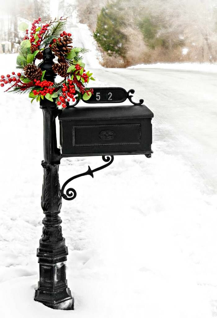 Black mailbox decorated with a Christmas wreath.