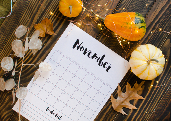 A November calendar on a table with fall decor, pumpkins and gourds.