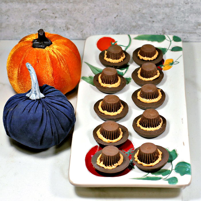 Pilgrim hat cookies on a plate with orange hat brims made of frosting and two velvet pumpkins.