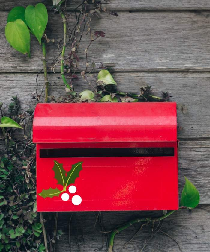 Decorating a mailbox for Christmas: Wall mount red mailbox with holly leaves and white berries and greenery.