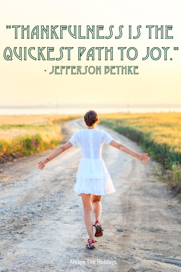 "A girl wearing a white dress walking down a dirt path in the sunset with a grateful Thanksgiving quotes text overlay reading ""Thankfulness is the quickest path to joy.""."
