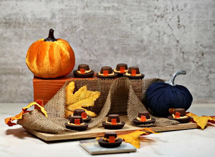 Display of pilgrim hat cookies with pumpkins, burlap and leaves.