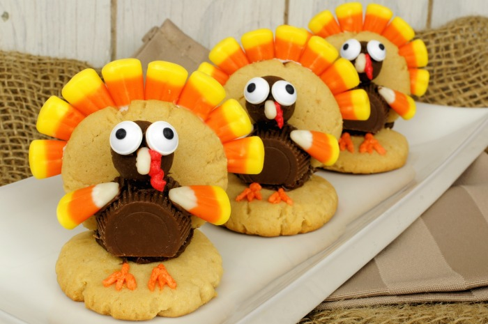Three turkey cookies in a row made with sugar cookies and candy.