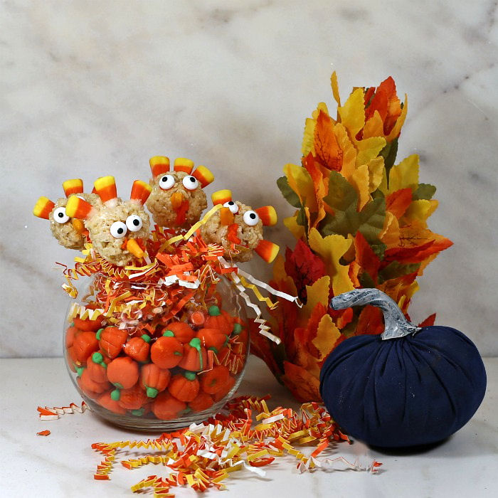 Rice Krispie turkey pops in a bowl of candy pumpkins and paper with a leaf tree and blue velvet pumpkin.