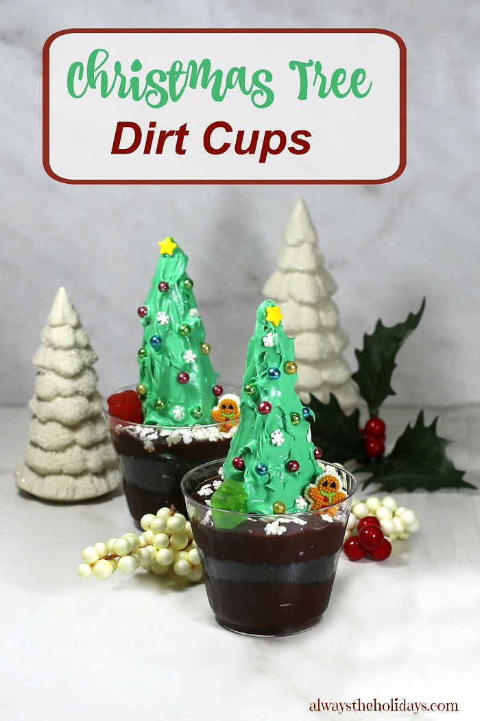 "Dirt pudding with Christmas trees, with porcelain white trees, holly and words reading ""Christmas tree dirt cups."""