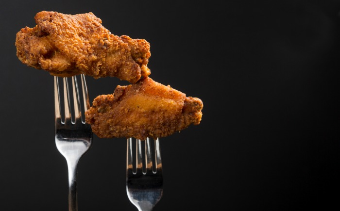 Two forks holding breaded, fried chicken wings and flats.