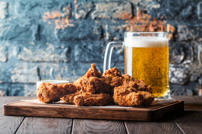 Tray of chicken wings and mug of beer against a blue brick wall to celebrate Super Chicken Wing Day.