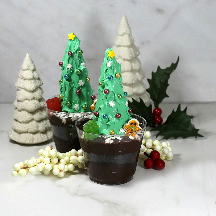 Christmas tree chocolate dirt pudding cups with porcelain trees and Christmas decorations.