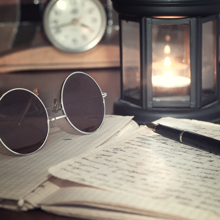Handwritten letters, a candle, clock and sunglasses arranged on a table to celebrate National Letter Writing Day.