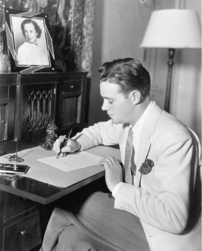 An old black and white photo of a man wearing a suit, sitting at a desk writing a letter.