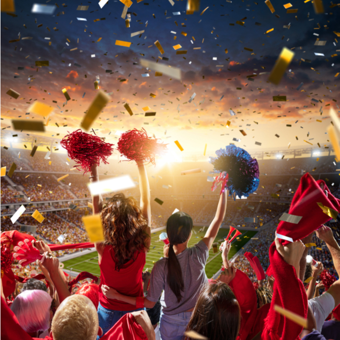 People cheering for each other, and celebrating success on New Year's in a football stadium.