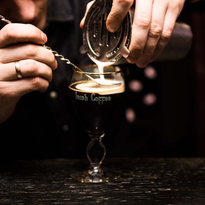 A bartender pouring an Irish coffee cocktail.