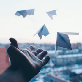 A man's hand letting go of paper planes symbolizing goals, wishes and resolutions from the window of a building in the city.