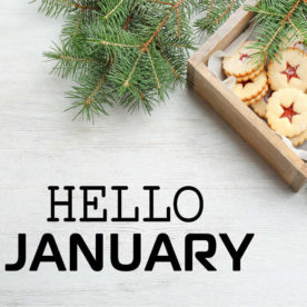"""Cookies on a wooden tray with fir boughs and text reading """"hello January."""""""