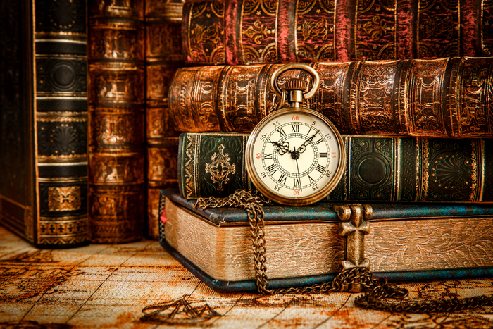 A stack of vintage books with a pocket watch to celebrate historical trivia.