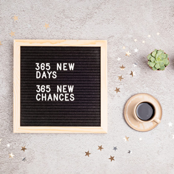 """A message board reading """"365 new days, 365 new chances"""" on a white counter next to a cup of coffee and a succulent to celebrate Stick to Your New Year's Resolutions Day."""