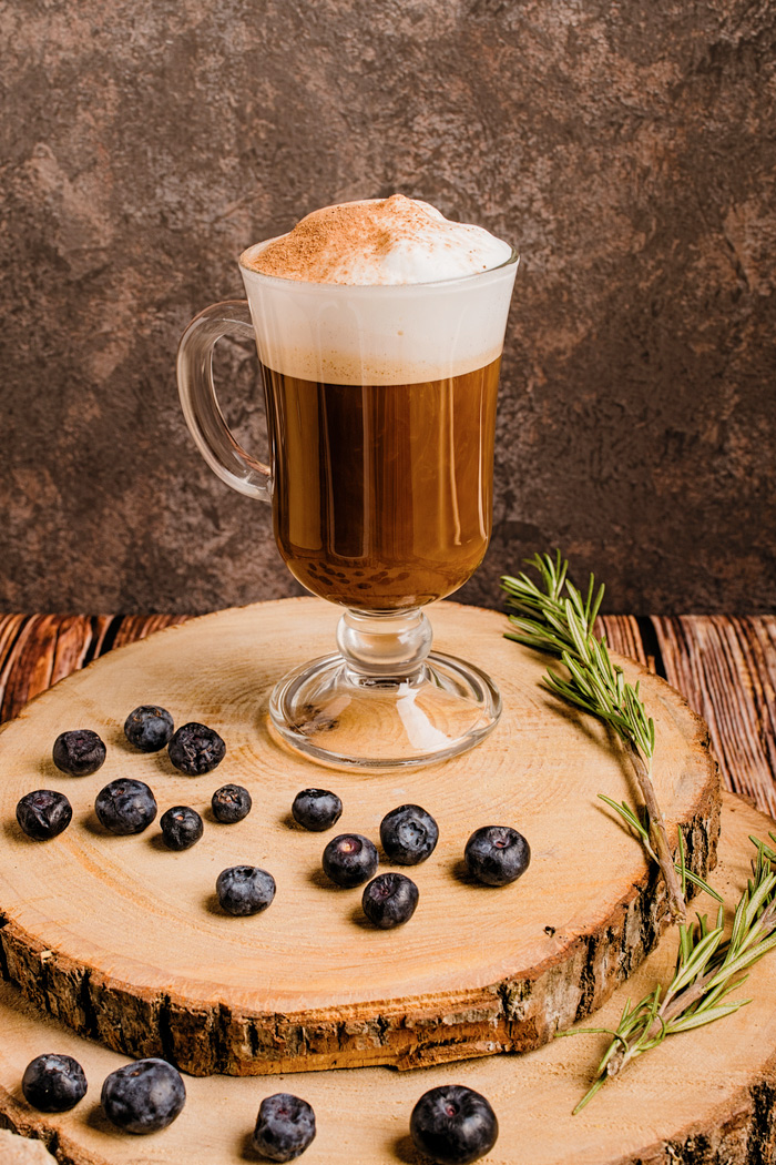 Irish coffee on a wooden board with blueberries celebrating Irish coffee history.