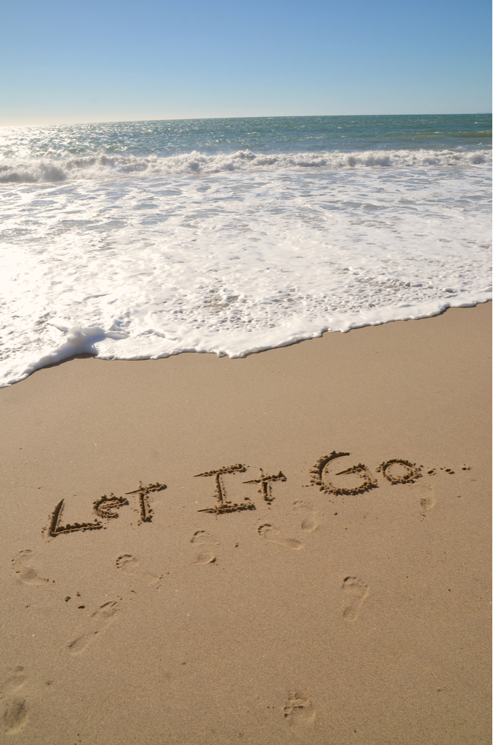 """The words """"let it go..."""" carved in the sand at the beach waiting for a wave to wash them away."""