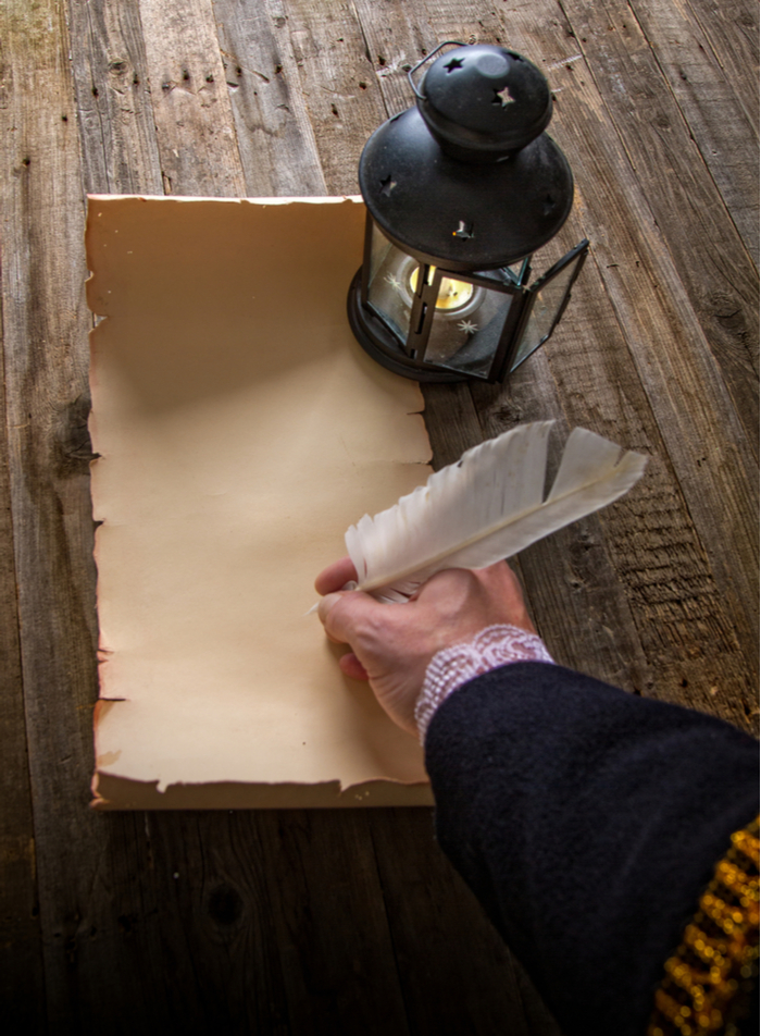 Man's hand with a quill and parchment for National Handwriting Day.