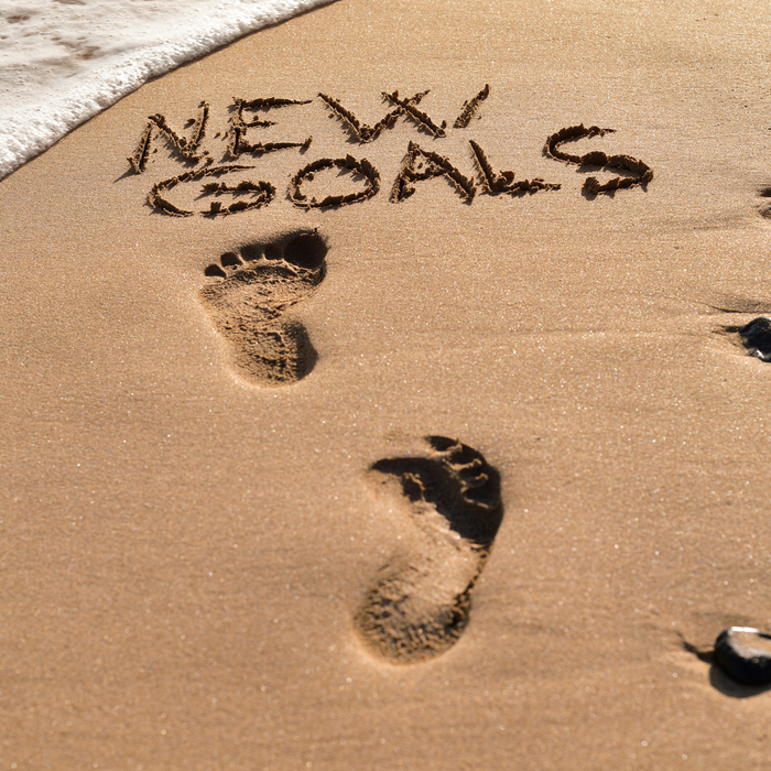"""Footprints on the beach leading to the text """"new goals"""" to celebrate Stick to Your New Years Resolution Day."""