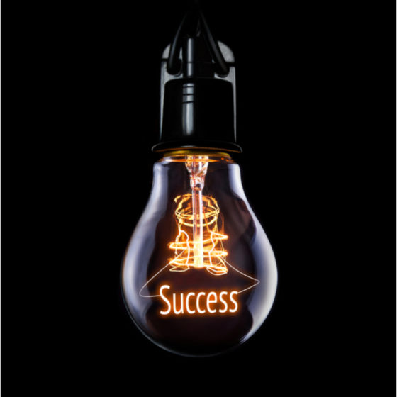 """A lightbulb that reads """"success"""" shining for someone who found the best New Year's resolution."""