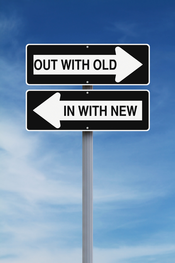 """Two one ways signs, the one pointing to the right reads """"out with the old"""" and the one pointing to the left read """"in with the new""""."""
