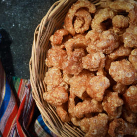 Bowl of pork rinds and a striped towel.