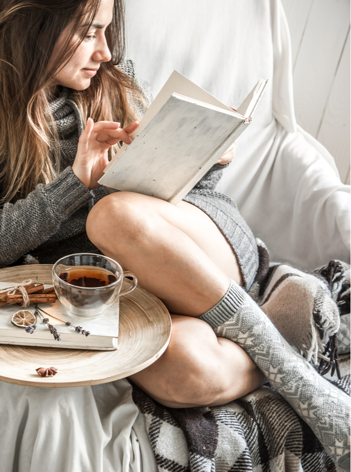 A woman practicing self care and reading as a reward to celebrate keeping New Year's resolutions.