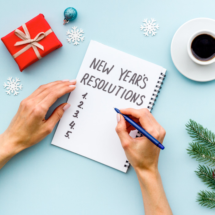 A person writing their New Year's Resolutions with various items in the background, a present, coffee and a Christmas tree branch.
